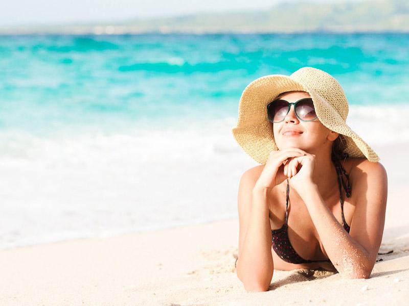 zaffy-mulher-deitada-na-praia-tomando-banho-de-sol-sorrindo-de-chapeu-oculos-escuros